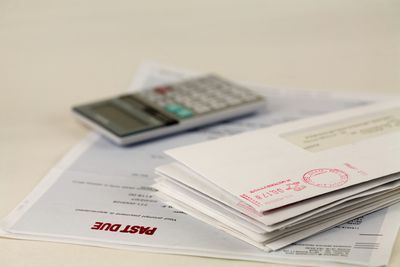 A billing statement with a past due stamp lies under a stack of bills and a calculator