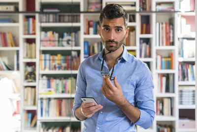 Portrait of sceptical young man with smartphone standing in front of bookshelves