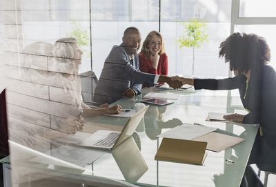 Businessman and businesswoman handshaking across conference table in meeting