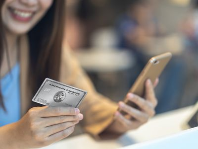 Woman holding iPhone and an American Express Business Platinum card.