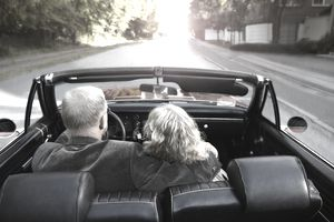 Mature couple driving convertible car in sunset