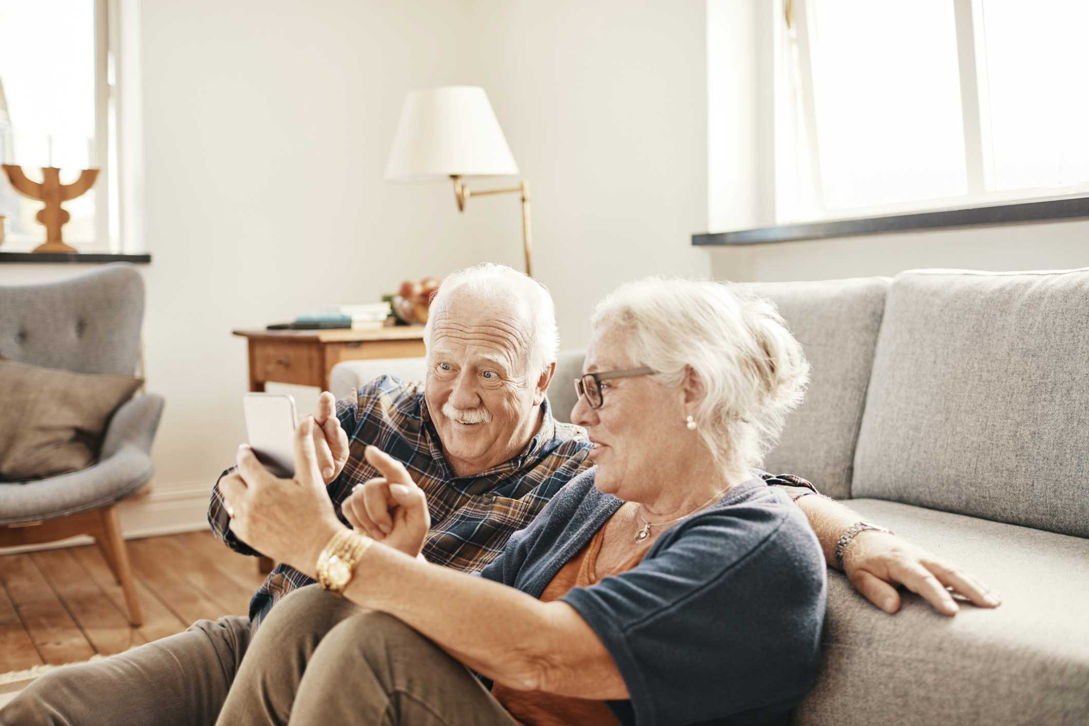 An elderly couple speaking to their beneficiaries over the phone.
