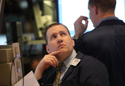 Traders work on the floor of the New York Stock Exchange before the closing bell May 6, 2010. The Dow plunged almost 1000 points before closing down about 350 on Greek debt fears