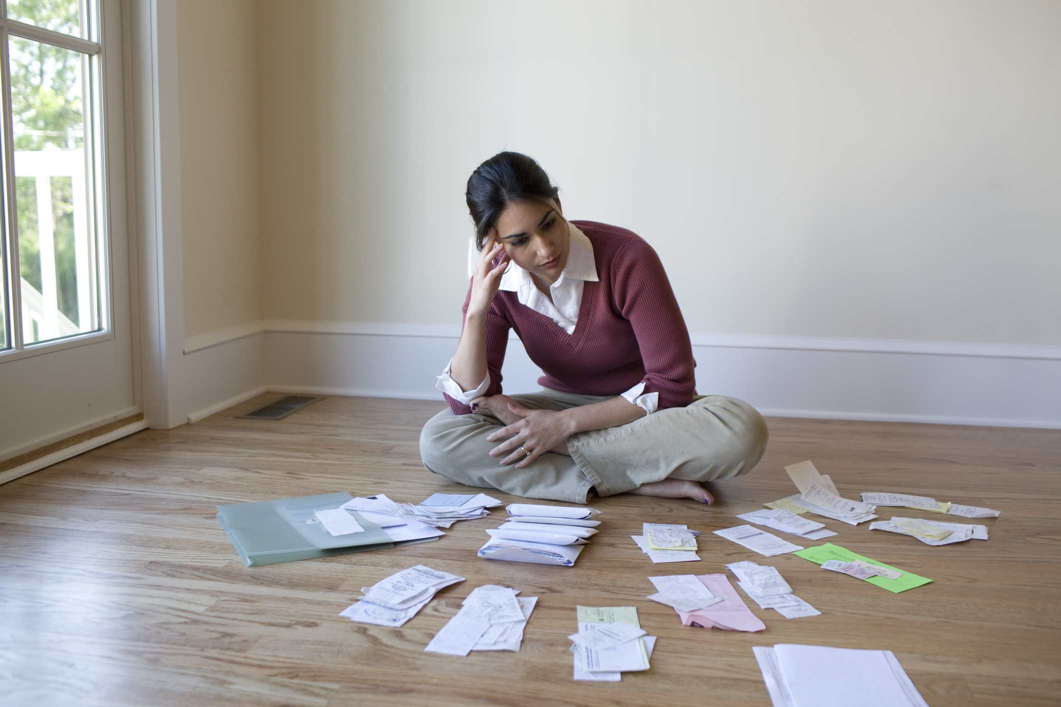 Woman taking inventory of bills in small piles