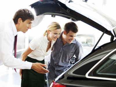 Young couple looking trunk of car with salesman