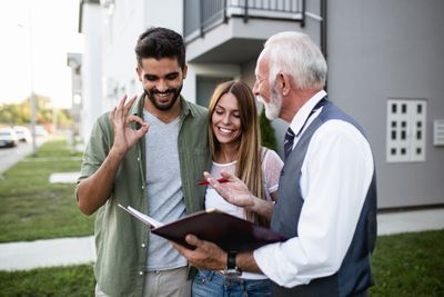 Happy couple examining documents with agent to sell house