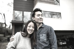 A young couple in front of a home.