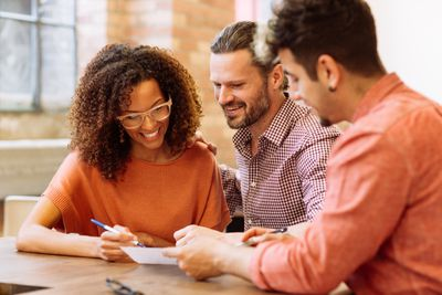 Smiling woman and man sign a loan estimate with an agent