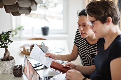Two women discussing financial documents while using laptop at table.