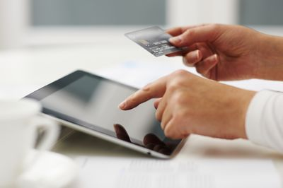 A person entering their credit card number into a tablet to buy something online.