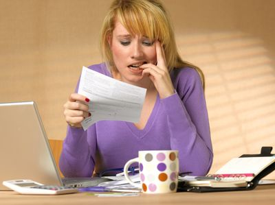 A worried woman reads a credit card statement as she bites her finger.