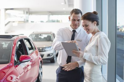 A man and a woman review a document in a car dealership.
