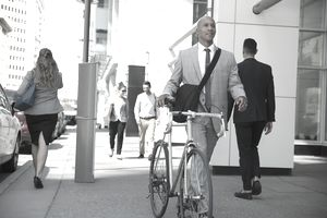 a businessman in a suit walking to work with his bicycle
