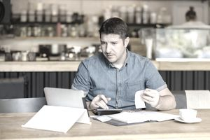 Small business owner calculating invoice payments using a laptop and calculator