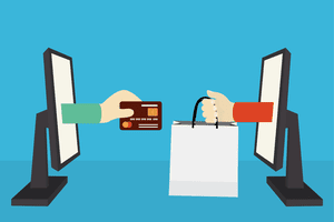 hands exchanging credit card for shopping bag through computers