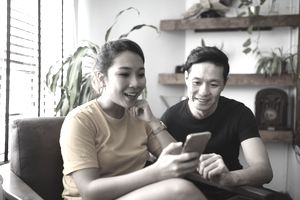 Couple reading from a smart phone together at home
