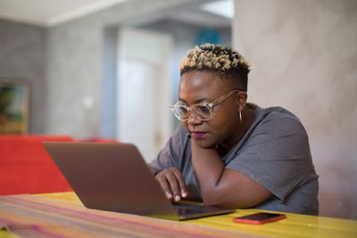 Black woman looking closely at laptop.
