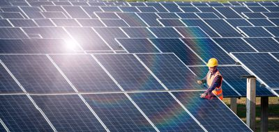 Worker standing in a field of solar panels, representing clean energy