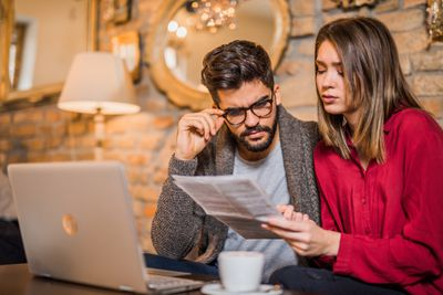 Young couple looking worried as they review a student loan statement while sitting in a coffee shop
