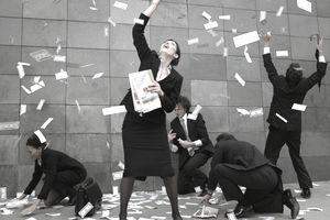 People trying to catch money floating all around them and on the ground.