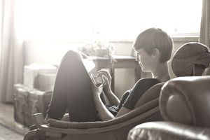 Young woman curled up on chair uses digital tablet