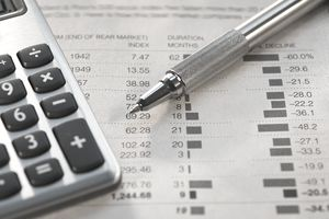financial information with pen and calculator