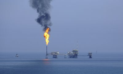 Burning gas off from the top of a vent pipe at an oil platform in the Gulf Sea