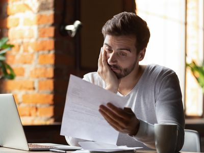 Confused frustrated man reading letter in cafe, receiving bad news.
