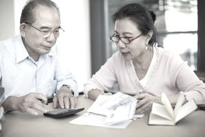 Senior couple working with bills at table