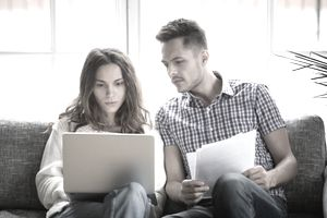A couple looks over the details of a bounced check.