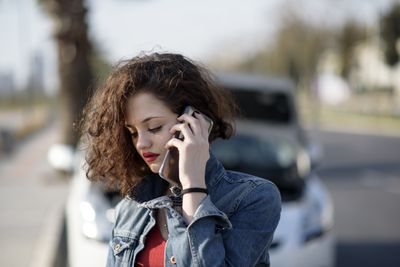 Woman standing near a car on a street, talking to an insurance adjuster after being involved in a car accident.