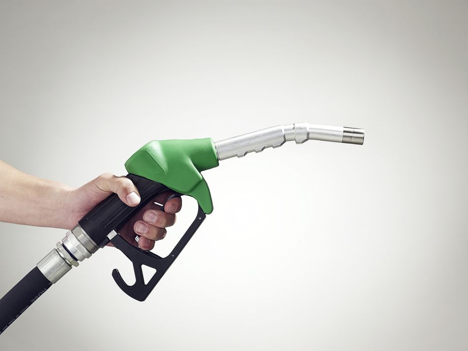 A hand holds a gas pump nozzle