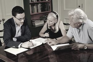 Senior couple looking over documents with financial advisor to see how much they need in savings to retire.