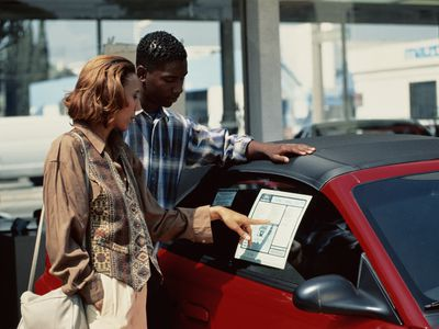A man and a woman looking at pricing details on a car.