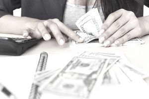 Business and finance concept. Closeup hand counting money in workplace.
