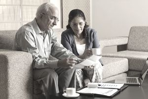 Older couple working in living room, with laptop on coffee table