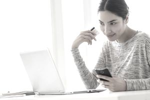 Woman with credit card, phone and laptop