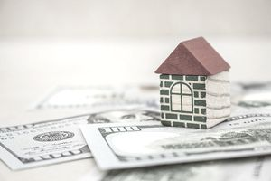 Small toy house on top of several large bills representing making money from investing in real estate.