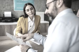 Male and female colleagues discussing paperwork at conference table