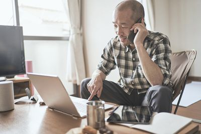 A man talks on the phone and looks at his computer as he manages his investments