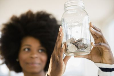 Woman holds jar of coins