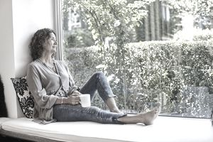 Middle-aged woman with curly hair sitting on windowseat cushion with tea mug looking out a window.