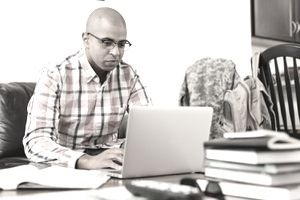 A soldier in civilian clothing with his uniform in the background taking online courses under the G.I Bill for College Tuition.