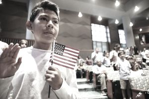 A boy with a flag in his left hand raises his right and intones an oath of citizenship.