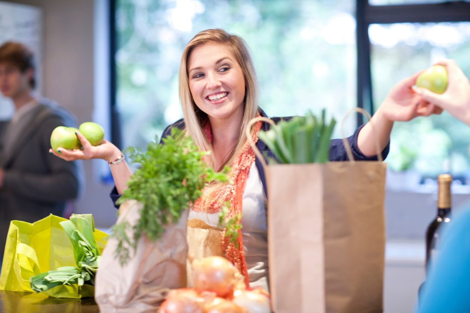A Woman Holding Fruit in Both Hands at Grocery Store