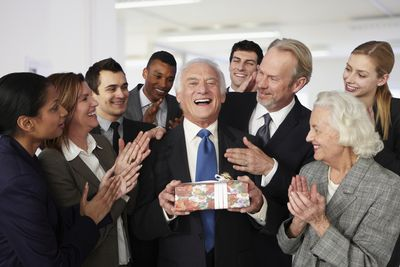 Coworkers gather around a retiring member holding a gift and clap as the pose for a photo