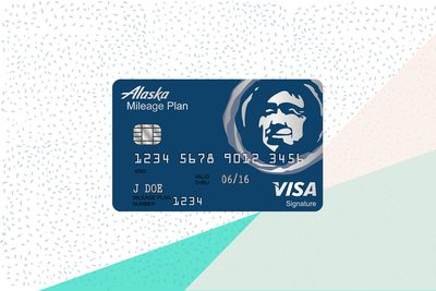 An illustration of the front side of an Alaska Airlines Visa Signature credit card shows the familiar Alaska Airlines logo of a grinning indigenous Alaskan.