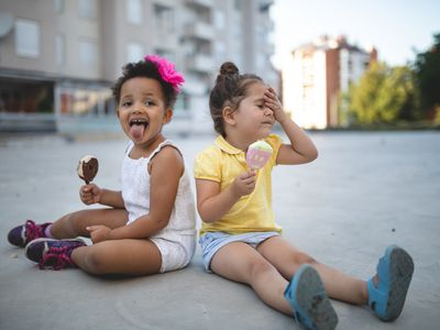 Two little girls sit on the sidewalk and enjoy melting ice cream novelties on a hot day. One of them appears to be experiencing