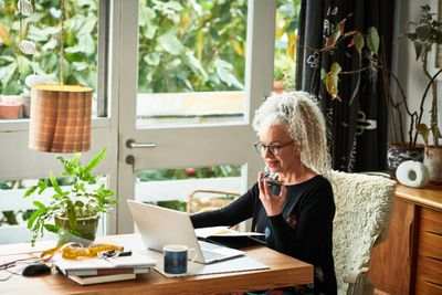 Cheerful senior businesswoman speaking on smart phone in front of laptop