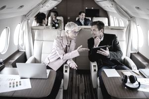 woman explains to man holding tablet on private airplane